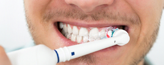 close up of man brushing his white teeth with electric toothbrush