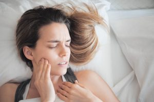 woman in bed holding face painfully
