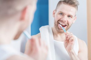 man brushing his teeth smiling