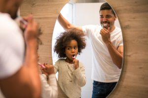 Father daughter brush their teeth to lower risk of COVId-19